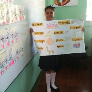 A girl in a school uniform holds up a poster with drawings of various objects with labels in Spanish.