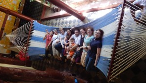 Eight adults and two children lay on a large blue and white striped hammock.